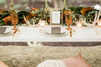 08 The table decor was done with a lush greenery and magnolia leaf garland, candles, antlers, colored glasses and elegant cutlery