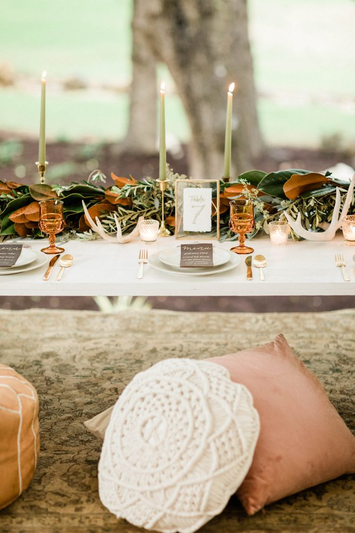 The table decor was done with a lush greenery and magnolia leaf garland, candles, antlers, colored glasses and elegant cutlery