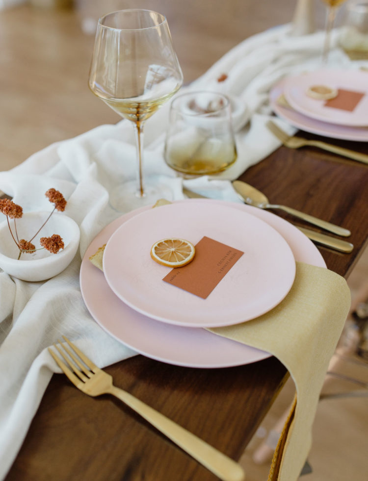 Matte pink plates and chargers, gold cutlery and colored glasses made up the look