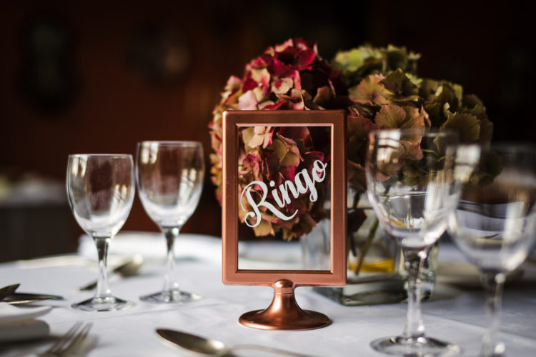 Rust hydrangeas and copper frames with table names were added to the decor