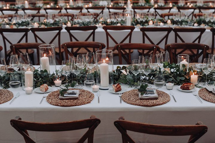 The tablescapes were done with greenery runners, tall candles and woven placemats