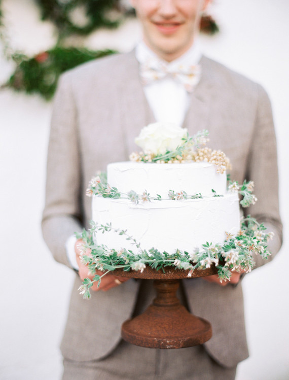 The wedding cake was a white textural one decorated with greenery and blooms plus berries on top