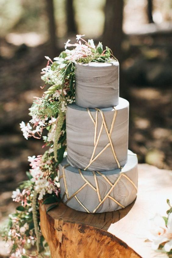 a grey marble wedding cake with gold geometric patterns and cascading greenery and blooms for a super trendy look