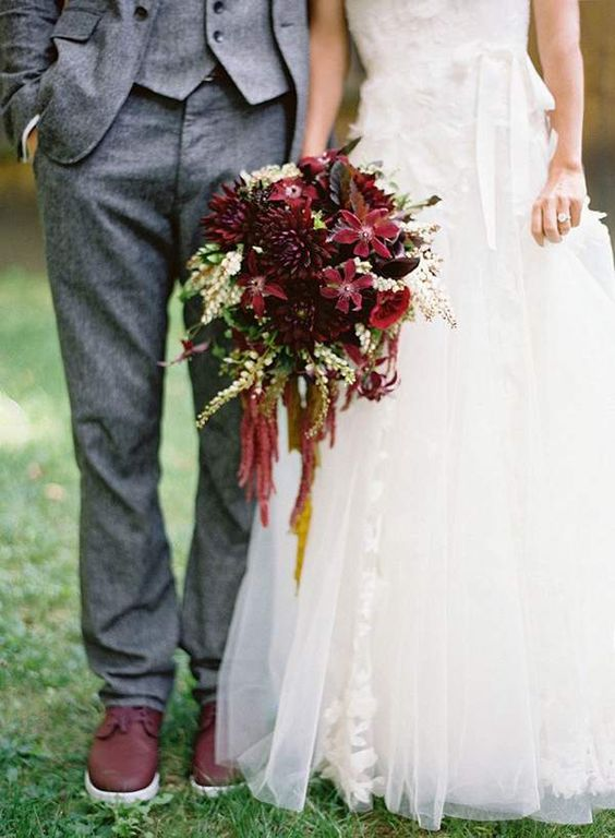 a grey three-piece suit paired with burgundy sneakers and a burgundy bridal bouquet