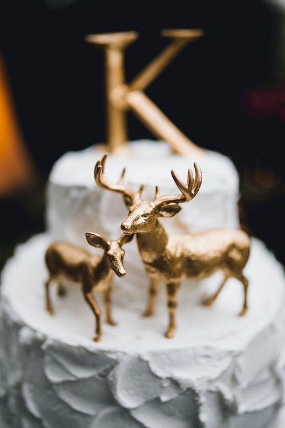 metallic gold deer cake topper with a large letter on top is what you need for a woodland or rustic wedding