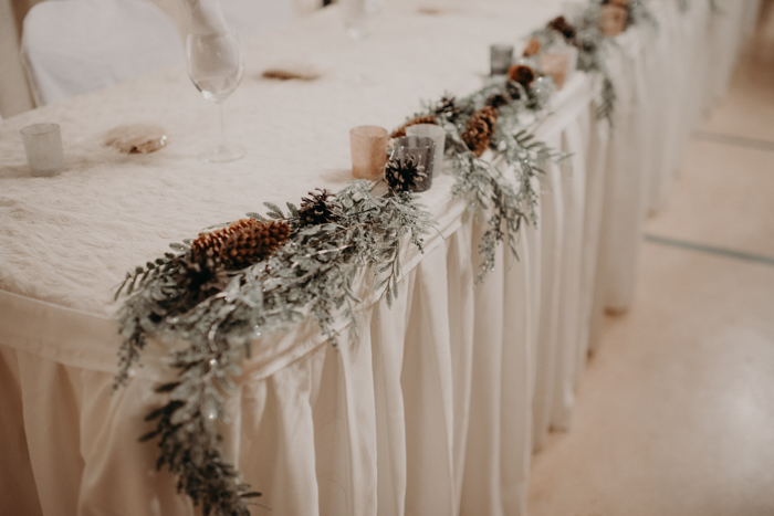 The reception tables were decorated with pale greenery, pinecones and candles