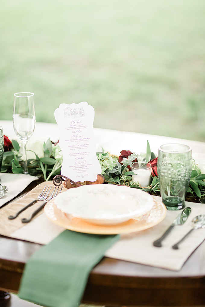 The wedding tablescape was done with a floral and greenery runner, elegant plates and chargers