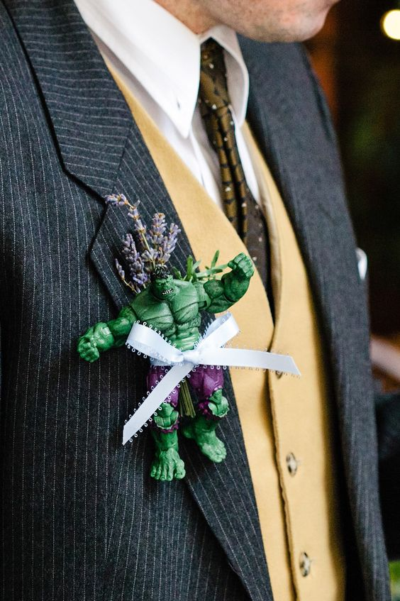 a Hulk boutonniere with lavender, greenery and a ribbon bow raises this groom's outfit to a new level