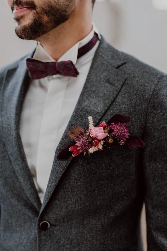a grey tweed suit, a burgundy bow tie and a floral boutonniere in pink and burgundy