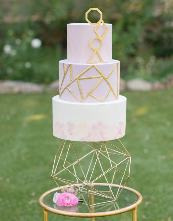 a lavender geometric wedding cake with gold patterns and a marbled tier plus a bold geometric cake stand