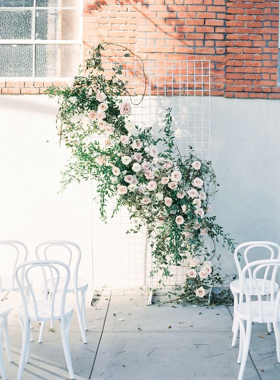 white wire mesh with a creative flower and greenery decoration on it, blush roses create an airy feeling