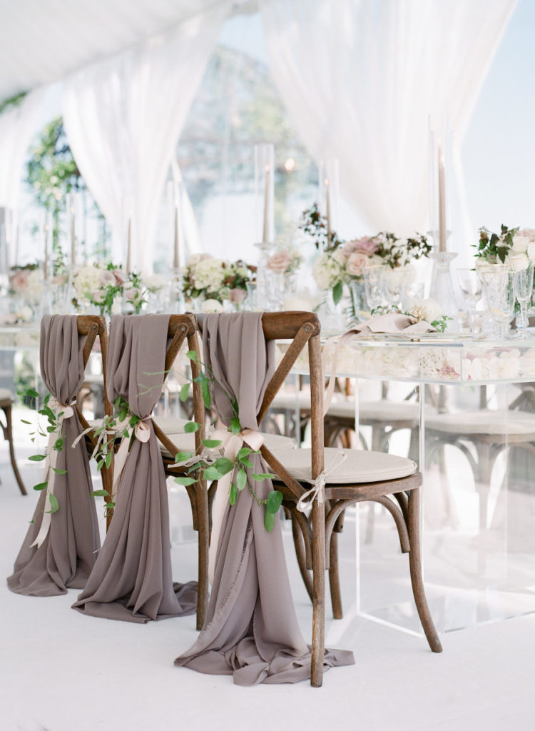 The chairs were decorated with taupe hangers, foliage and blush ribbons for a sophisticated feel