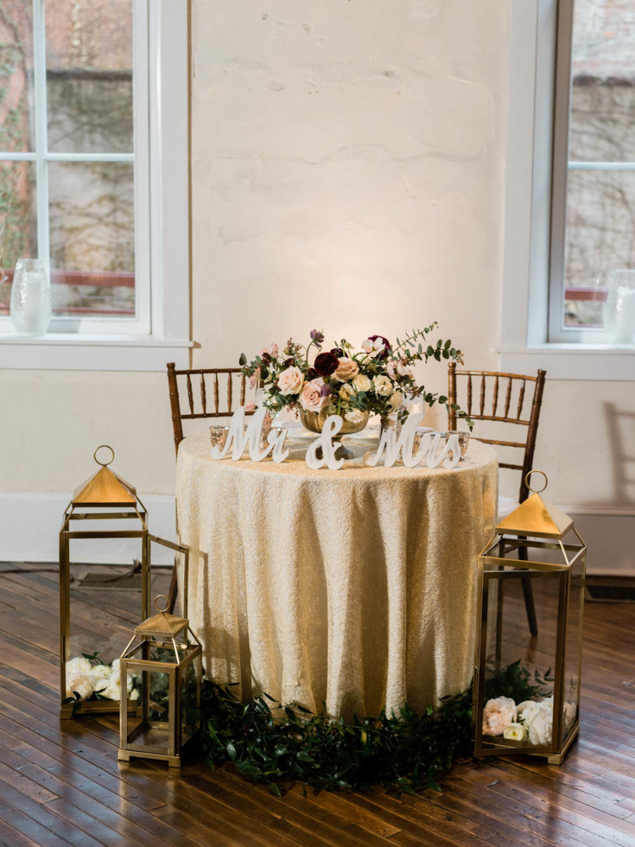 The sweetheart table was styled with greenery, blooms, lanterns and calligraphy