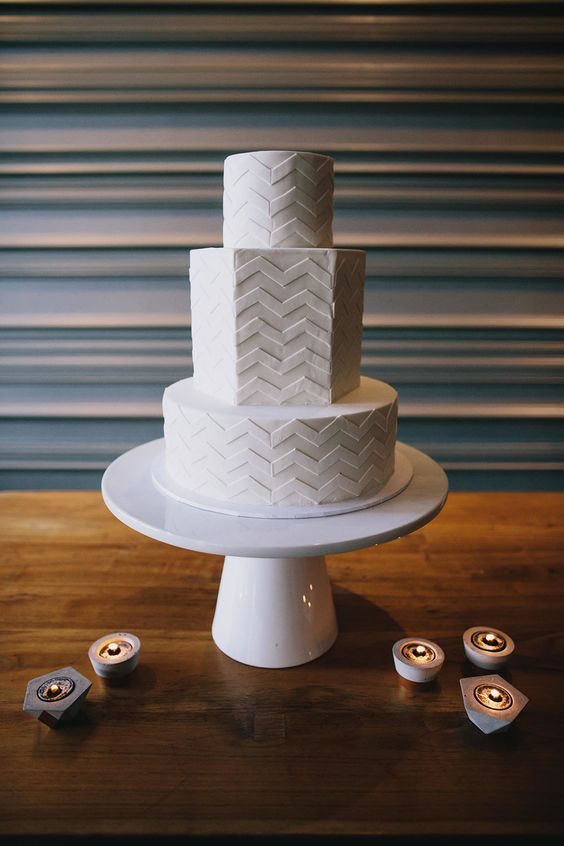 a modern geometric white fondant wedding cake with chevron detailing is a chic idea to rock