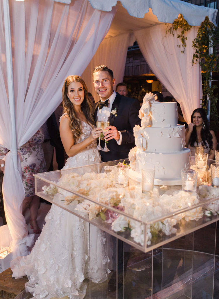 The wedding cake was a giant one with sugar flowers and it was presented on a clear glass stand filled with blooms