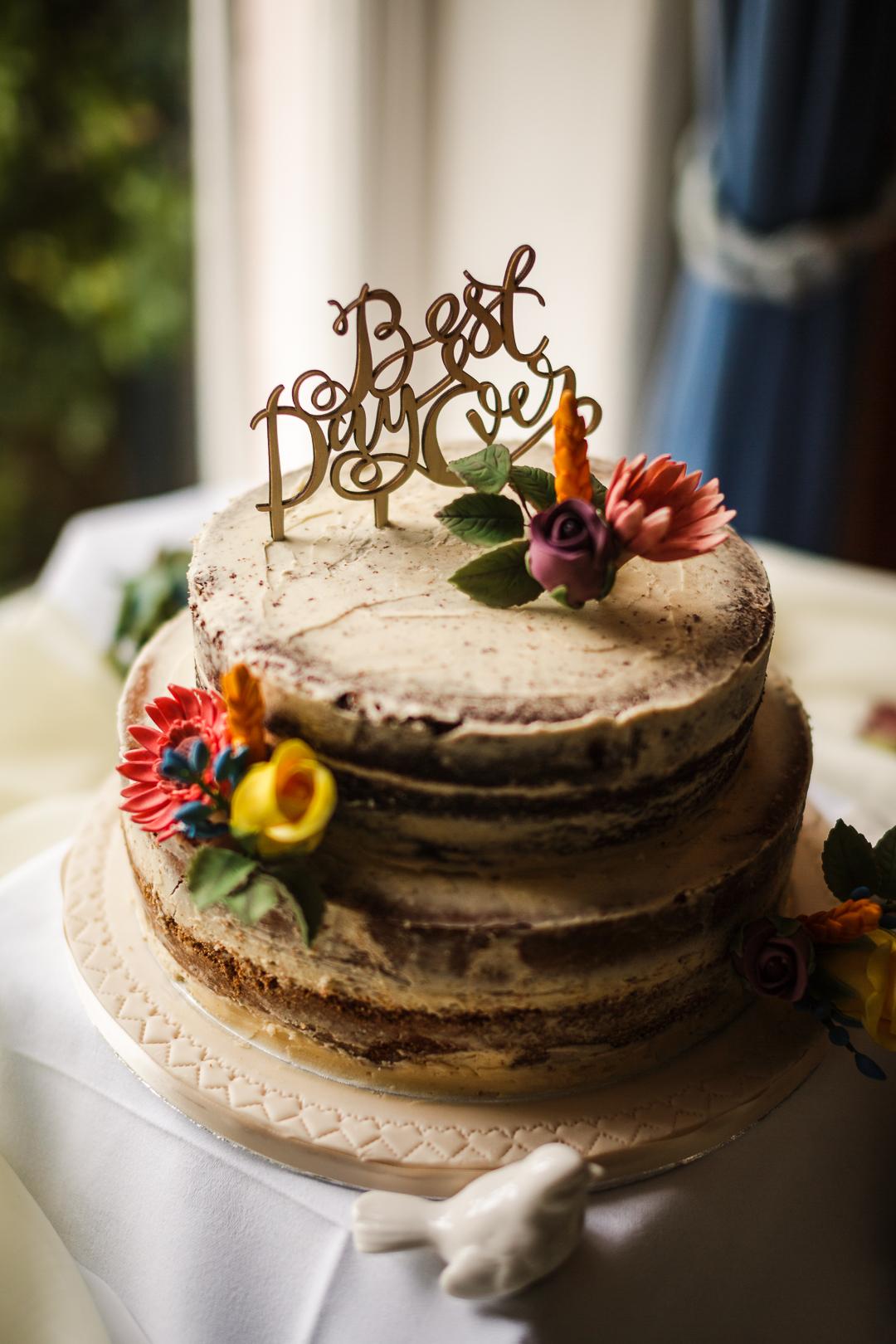 The wedding cake was a semi naked one, topped with a calligraphy topped and blooms