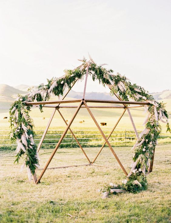 a geometric altar decorated with greenery and pampas grass is amazing for a boho chic or mid century wedding