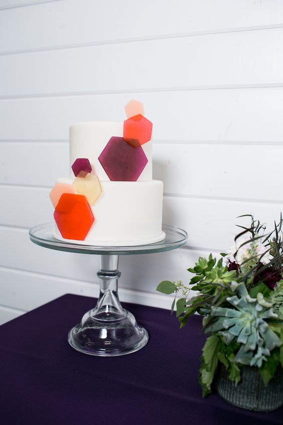 a pure white wedding cake decorated with colorful hexagons is a simple and timeless idea for a modern wedding