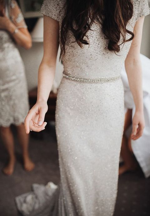 a silver sheath wedding dress with short sleeves and an embellished sash for a glam and sparkly touch
