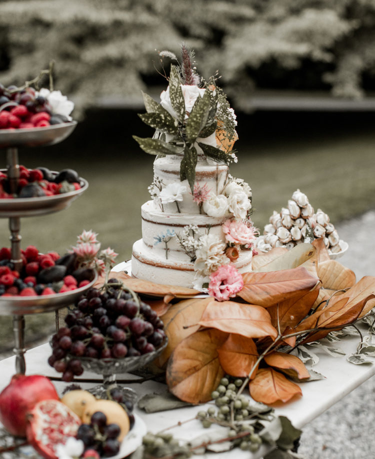 There was a fruit table with a naked wedding cake topped with flowers and foliage