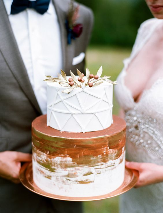 a two tiered wedding cake with a geometric layer and a berry topper plus copper leaf for an elegant feel