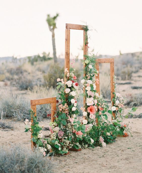 rustic wooden frames decorated with lush flowers and greenery for a desert space or a rustic feel at your backyard wedding