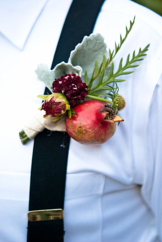 a pomegranate and bloom boutonniere with pale greenery for a fall rustic or farm to table wedding