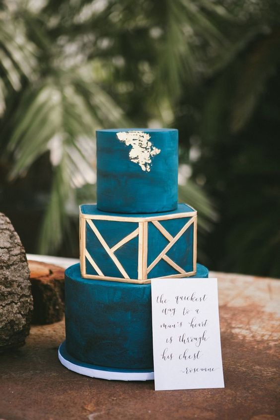 a watercolor teal wedding cake with gold patterns and gold leaf is a chic and bold idea for a tropical wedding