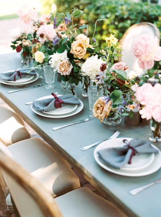 a grey and burgundy table setting is spruced up with lush florals of various muted shades