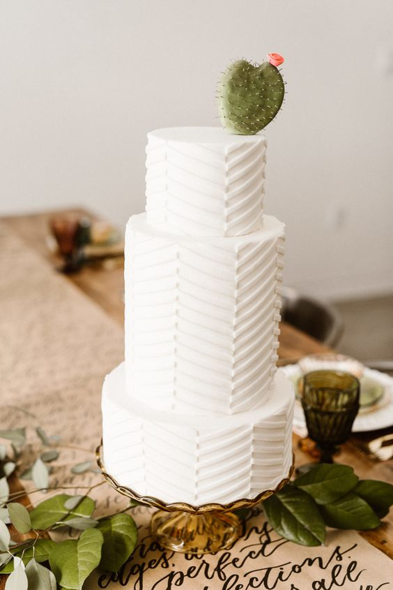 a white geometric wedding cake with a chevron pattern topped with an edible cactus is a bold idea for a desert wedding