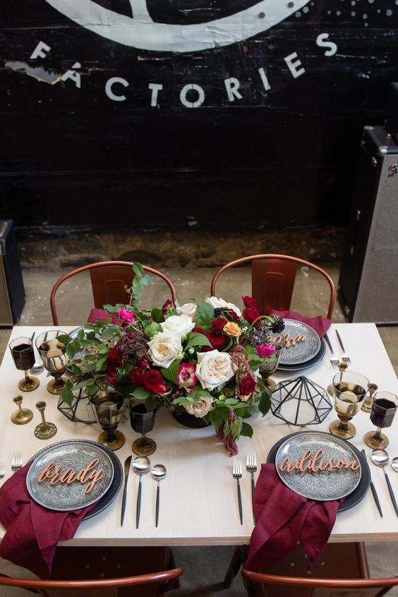 a gorgeous tablescape with an industrial feel, grey plates and chargrers and burgundy napkins and blooms for a chic look