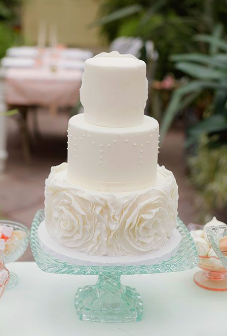 a whimsical three tier wedding cake with sugar flowers and pearls for a vintage feel
