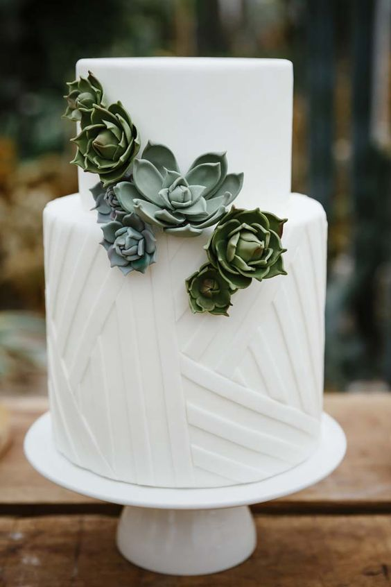 a white wedding cake with geometric patterns and sugar succulents as decor, two trends in one cake