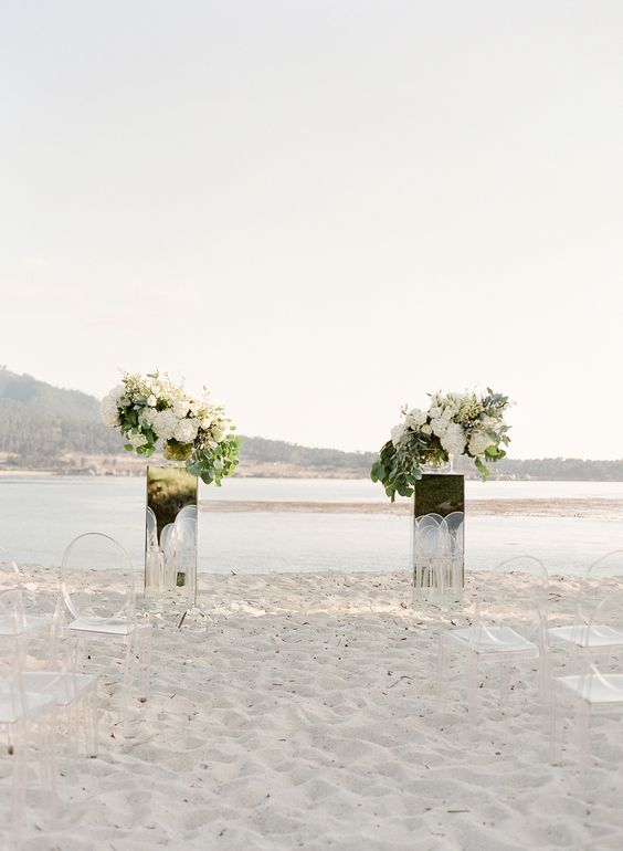 mirrored stands topped with lush white flower and greenery arrangements and a stunning beach backdrop for your wedding