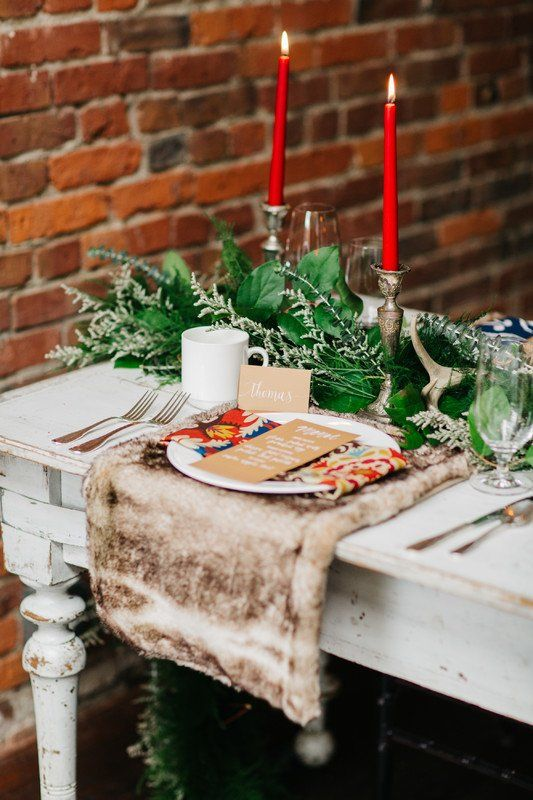 a greenery garland, red candles and fur place setting are amazing for a winter or a holiday wedding