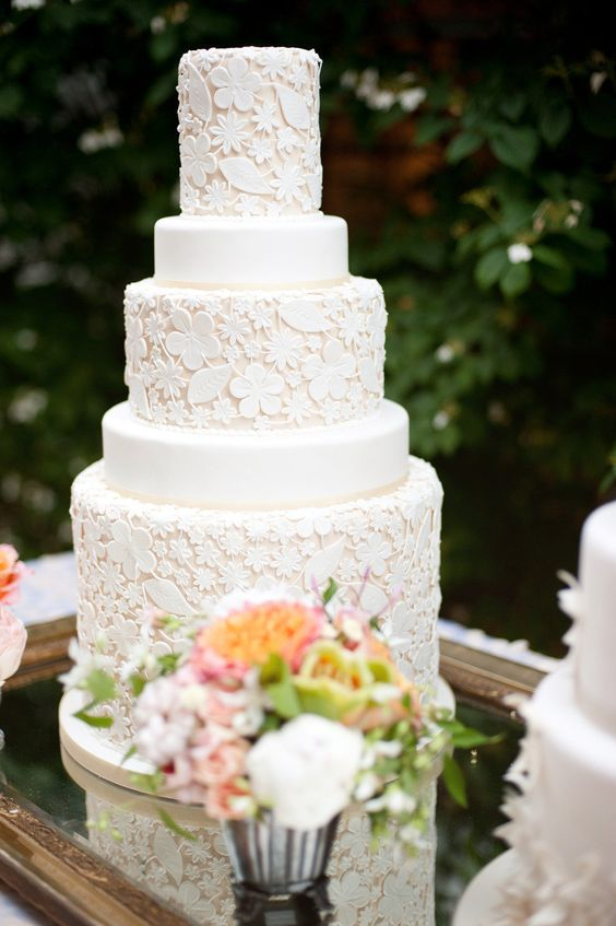 a white floral pattern wedding cake with plain tiers is a real masterpiece for a garden wedding