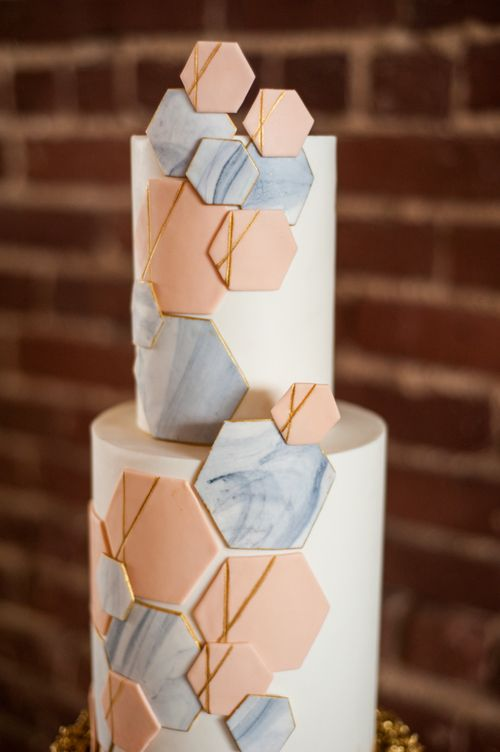 a white wedding cake with grey marble and coral hexagons plus gold touches is a chic idea for a modern wedding