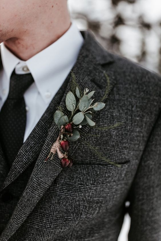 a winter boutonniere of greenery and burgundy berries is a fresh touch of color and frost at the same time