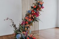 18 a copper wire wedding backdrop with a cascading floral installation in bright colors and greenery for an outdoor feel indoors