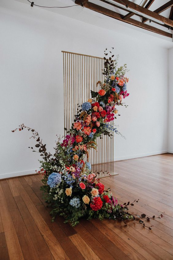 a copper wire wedding backdrop with a cascading floral installation in bright colors and greenery for an outdoor feel indoors