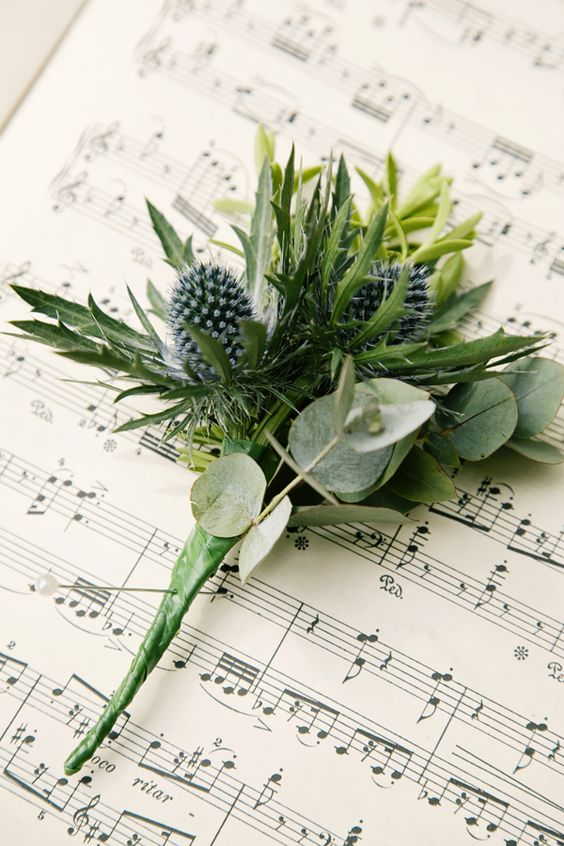 a greenery boutonniere spruced up with blue thistles for a textural look and a bold touch
