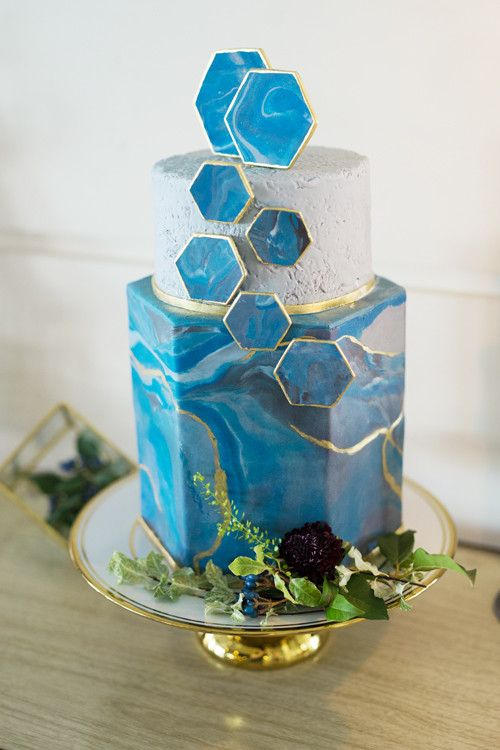 a blue marble and concrete-inspired wedding cake and marbleized hexagons with a gold edge