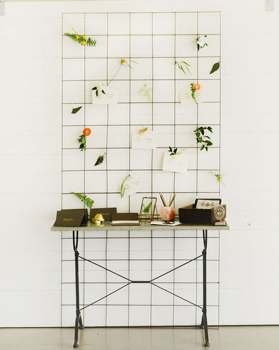 a grid with greenery and blooms and some guest wishes attached will make up a wedding decoration
