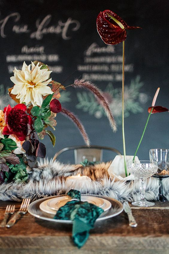 a luxurious decadent wedding tablescape with a faux fur table runner and dark blooms and herbs plus an uncovered wooden table