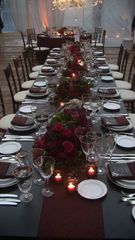 a refined reception table decorated with a grey tablecloth and menus, a burgundy table runner, napkins and flower centerpieces