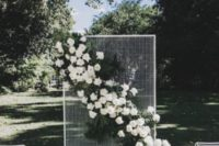 20 a framed mesh piece with a ush diagonal white flower and greenery wedding decoration for a chic modern wedding