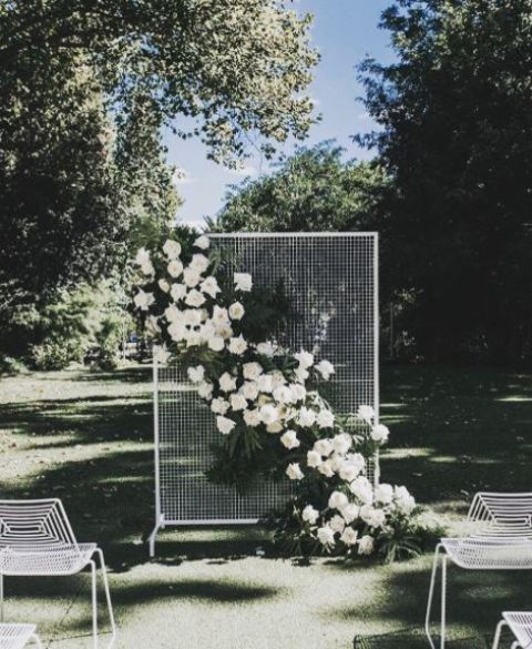 a framed mesh piece with a ush diagonal white flower and greenery wedding decoration for a chic modern wedding
