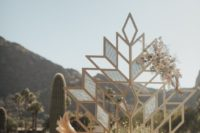 21 a gorgeous boho geometric wedding backdrop decorated with blooms and with pampas grass next to it for a boho ceremony