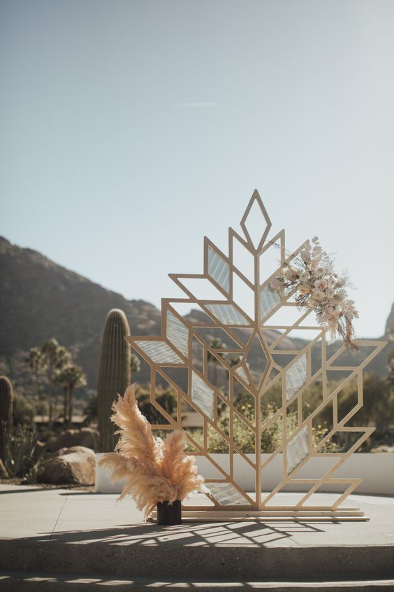 a gorgeous boho geometric wedding backdrop decorated with blooms and with pampas grass next to it for a boho ceremony