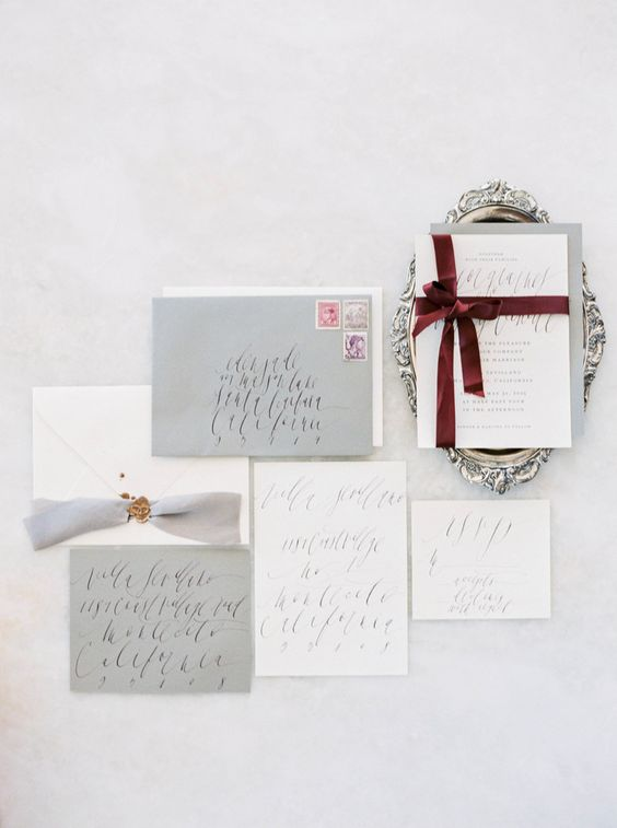 a simple grey and white wedding invitation with burgundy ribbons that make a colorful accent